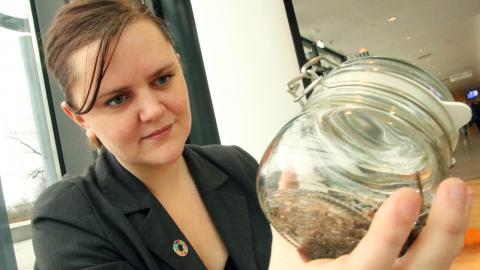 Nya forskningsresultat från Göteborgs universitet visar att mycket mikroplast kommer från större plastföremål som fallit sönder i havet. Forskaren Therese Karlsson håller upp en glasburk med en näve strandsand full med plastbitar.  Bild: Annelie Moran