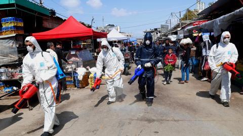 Arbetare desinficerar på Gazaremsan för att skydda mot spridning av coronaviruset.  Bild: Adel Hana/TT