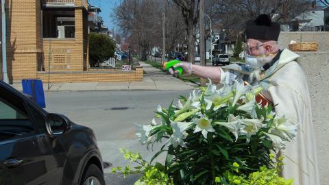 Prästen Timothy Pelc ger välsignelse med vattenpistol utanför St. Ambrose kyrka, i Michigan. Bild: Natalie White/AP