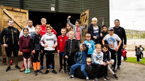 Träningsgruppen 8–13 år utanför förrådet på Kviberg där de visar speciellt intresse för ett vält traktordäck (som ingen av dessa ungdomar ännu orkar rubba).   Bild: Thomas Svensson