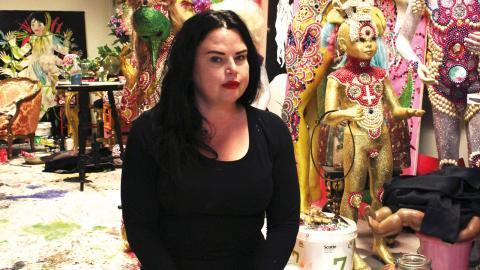 Konstnären och illustratören Linda Spåman dekorerar dockor med glitter, syntetiskt hår, pärlor och porslinständer.  Bild: Julia Sandstén Vikberg