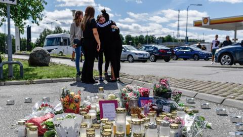 Folk samlas vid blommorna och ljusen på platsen där en tolvårig flicka sköts ihjäl vid en bensinmack i Hallunda i Botkyrka, söder om Stockholm förra söndagen.  Bild: Stina Stjernkvist/TT