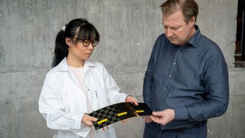 Doktor Johanna Xu och professor Leif Asp med en nytillverkad strukturell battericell. Cellen består av en kolfiberelektrod och en litiumjärnfosfatelektrod separerade med glasfibertextil.  Bild: Marcus Folino