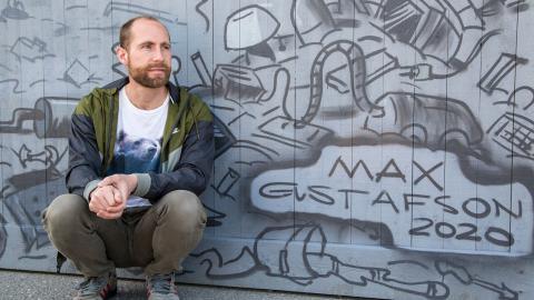 """Max Gustafson framför sin 25 meter långa målning på Korsvägen. Nyligen släpptes hans femte bok """"Homo Consumericus"""" och i dagarna kommer brädspelet """"Springvikarierna"""".  Bild: Gunnar Fägersten Novik"""