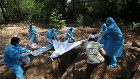 Frivilliga och sjukvårdare begraver en patient som fallit offer för covid-19 i Chennai, Indien. Bild: R. Parthibhan/TT