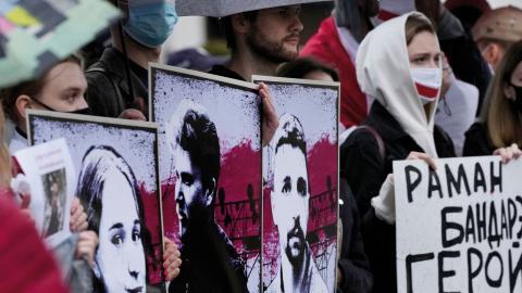 Demonstranter utanför Belarus ambassad i Polen håller upp bilder på fängslade aktivister. Bild: Czarek Sokolowski/AP