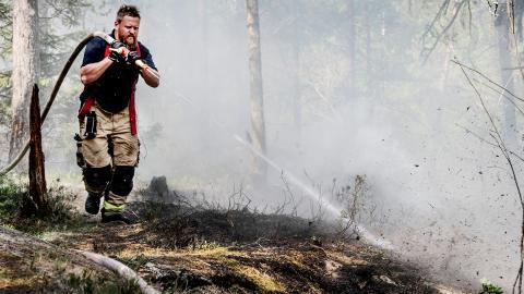 En brandman släcker en markbrand i Stortorp i södra Stockholm 2019.  Bild: Tomas Oneborg/SVD/TT