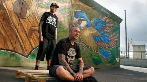 Christofer Siwertz-Svedjeby och Tony Boufadene är bägge tatuerare och graffitikonstnärer. 1 augusti arrangerar de Graffitins dag i Göteborg. Här poserar de framför en av Tonys målningar, belägen vid Stenpiren. Bild: Christian Egefur